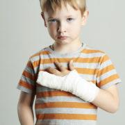 Trist gutt med bandasjert hand