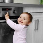 Barn som smiler framfor en ovn